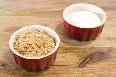 suggesting: Selective focus on bowl of brown sugar, with bowl of white sugar in the background, suggesting that brown sugar should be preffered