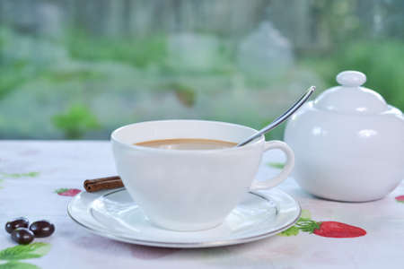cinnamon stick: Coffee with half and half is served, decorated with cinnamon stick and sugar bowl in the background