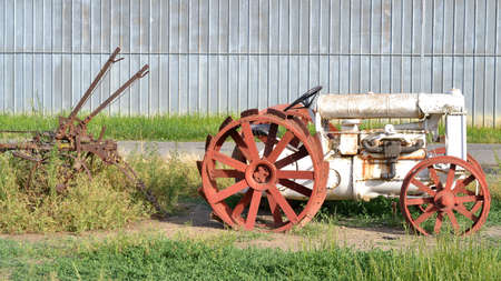 old farm: Old white tractor rusting away at old farm equipment graveyard