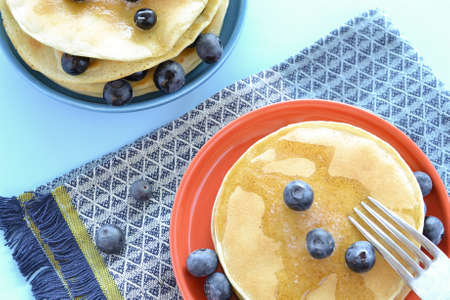Gluten free blubbery pancakes on blue table cloth Stock Photo