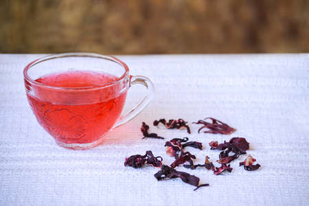 laxative: Cup of hibiscus tea in transparent cup on white tablecloth beside dried hibiscus flowers Stock Photo