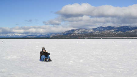 south lake tahoe: South Lake Tahoe, California, USA, 10 January 2016. Unidentified young man and crowd in the background enjoy the frozen waters of lake tahoe in the winter.