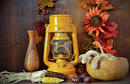 Abstract still life displaying dead, dried harvest symbols and a German gas lantern, against wooden background and decorated with colorful fall leaves