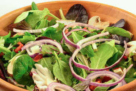 Organic mixed greens, red onion, mushroom and sprouted tofu salad served in wooden bowl, on white background Stock Photo