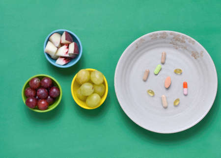 Dietary supplements, and fruits in colorful bowls, on greet tablecloth