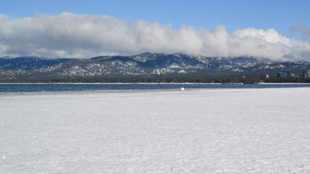 south lake tahoe: Frozen margins of South Lake Tahoe in the winter, with the tahoe basin mountains covered with snow in the background and clouds in the sky, California side, USA