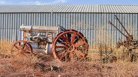 Old white tractor rusting away in old farm equipment graveyard on very dry California grass, against steel wall