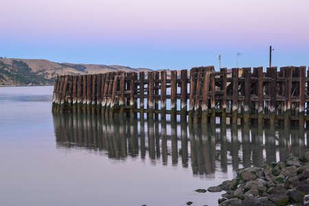 martinez: Sunrise at the waterfront of Martinez, California, USA, featuring the boat fence and its reflection, with the chaparral in the background