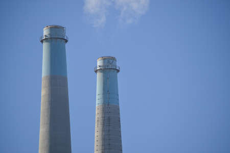 Upper portion of two stacks of a power plant producing smoke, against a blue, cloudless sky