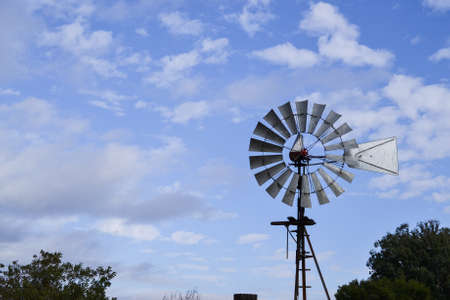 partly: Closeup on upper portion of Vintage Wind Mill in Central California against partly cloudy sky Stock Photo