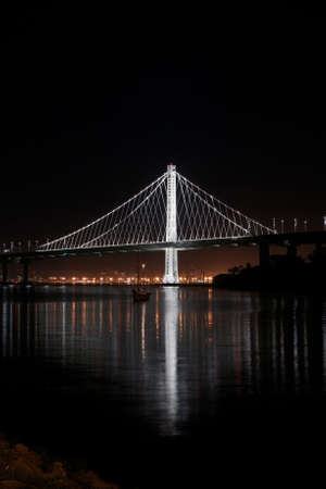 Long exposure photo of the New East Span Bay Bridge illuminated  at night, reflecting glowing lights of the city behind it. Iconic and majestic bridge after dark viewed from Treasure Island in San Francisco.