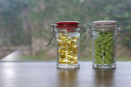dietary supplements: Two transparent glass bottles of dietary supplements (fish oil oyster-shell calcium) and on a windowsill, against a dirty window Stock Photo