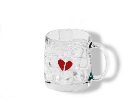A broken red heart frozen inside a transparent cup filled with ice cubes and water, suggesting the concept of being rejected by ones object of love and affection- isolated on white
