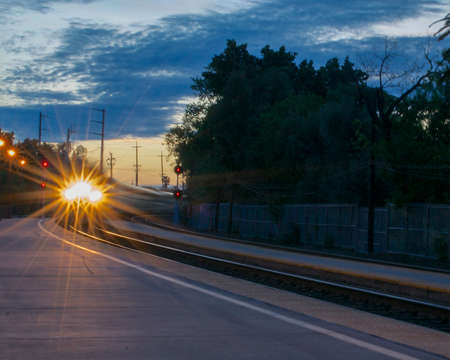 A passenger train is fast approaching the station in the crack of dawn Stock Photo
