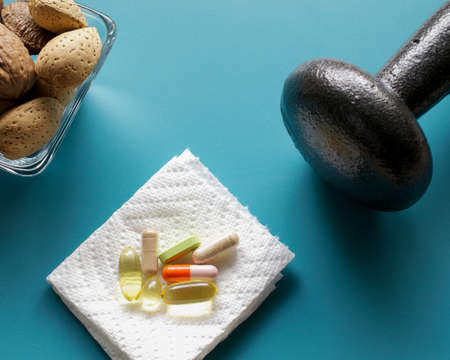 Closeup on dumbbell, nuts and dietary supplements on blue background: fitness and weight loss concept.