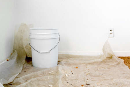 floor covering: A white bucket over a sheet of plastic placed over carpet floor to collect water from leaking ceiling