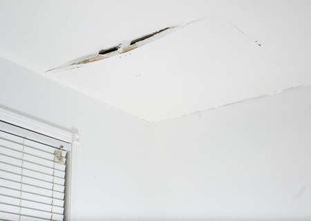 Close-up op een spleet in een wit plafond van een generiek, niet-geïdentificeerd oud huis, als gevolg van waterlekkage, met een opgebold paneel dat dreigt af te vallen Stockfoto - 70957173