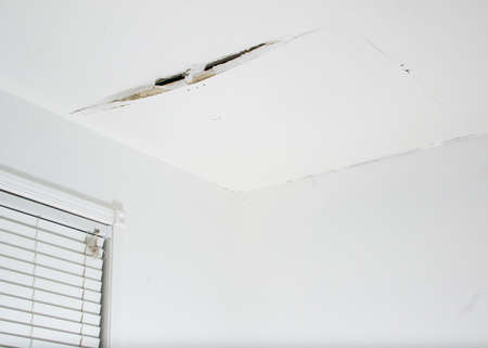 Closeup on a crack in a white ceiling of  a generic, unidentified old house, resulting from water leak, showing a bulged panel that in danger of falling off