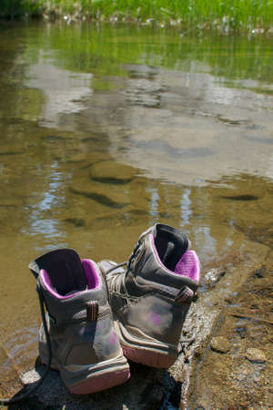 Pair of old, dusty hiking boots on a rock at the margin of a lake, suggesting that its owner is taking a swim - adventure in the outdoors concept Stock fotó