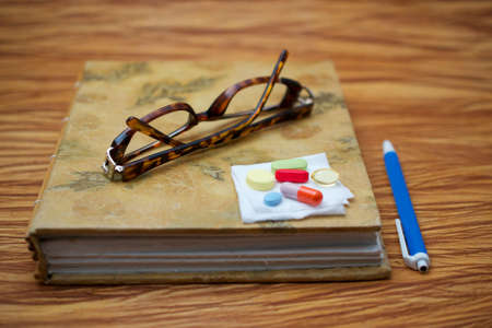tiredness: A pair of broken reader glasses on closed journal and a pen on wooden table, suggesting an elderly person taking a break to take medication