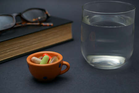 A pair of broken reader glasses resting on a closed book,  a bunch of pills in a bowl and a cup of water on dark background, suggesting an elderly person taking a break from reading to take medication Stock fotó