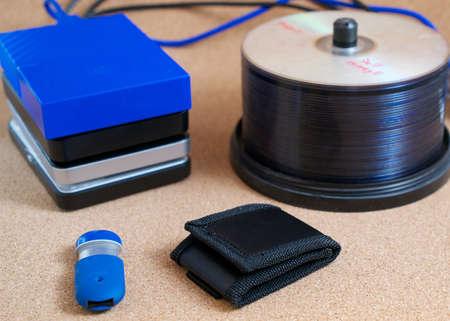 Digital data backup devices: external USB hard drives, memory stick, memory card wallet and CDs on cork background Reklamní fotografie