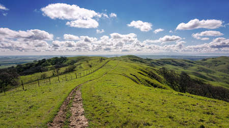 Panoramic view of a trail at the Lagoon Valley Park in Vacaville, California, USA, running along a fence, featuring the chaparral in the winter with green grass, and clouds Stock Photo