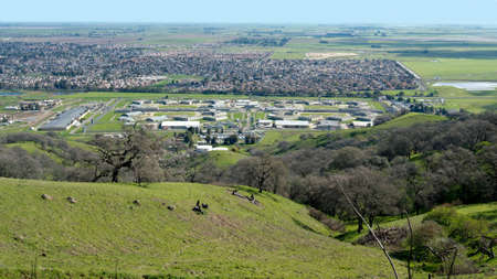 Panoramic aerial view of Vacaville and State Prison from Lagoon Valley Park, California, USA, featuring the chaparral in the winter with green grass