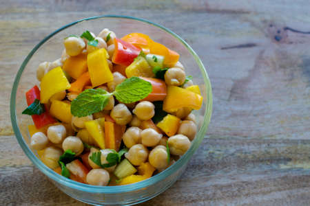 Garbanzo bean salad in transparent glass bowl- healthy eating concept