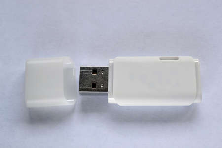 A white USB memory stick on a white piece of paper, with the lid off Stock fotó