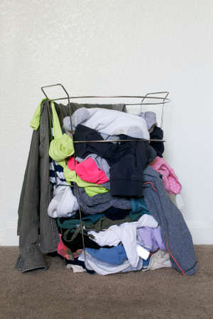 sac: Metal laundry basket full with colorful dirty clothes against white wall background, on brown carpet