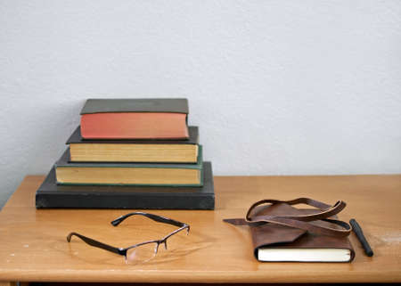 Leather journal, pencil, readers, and hardbound, used books stacked on a weathered, used wooden desk, against white wall - unplugged study concept Stok Fotoğraf