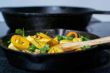Zijaanzicht van houten lepel die tofu, faro en groenten in gietijzerkoekepan bewegen - het concept van het veganistvoedsel