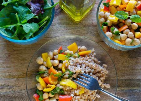 Een maaltijd die bestaat uit farro, garbanzo bonen salade en gemengde greens geserveerd met olijfolie op houten tafel gezonde veganistisch eten concept
