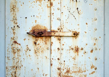 Detail of an old, rusty steel door painted white at Fort Baker in San California, California, USA, with a lock system
