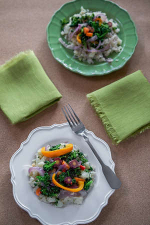 Closeup  on paleo vegan dish of cauliflower Rice Stir-Fry on white plate, on wooden table set with green napkins, and another, green plate in the background- eating healthy concept