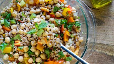 Een salade bestaande uit farro, garbanzo bonen, paprika's en lente-uitjes geserveerd met olijfolie op houten tafel-gezonde vegan eten concpet Stockfoto - 82824809