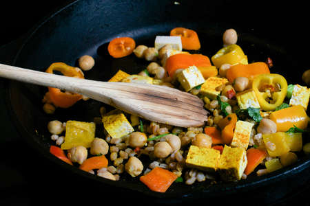Closeup on weathered wooden spoon stirring bell pepper, tofu, farro and garbanzo beans mix in cast iron skillet with a - healthy cooking concept