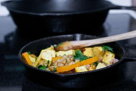 De hoekmening van het diner van houten lepel die tofu, faro en groenten in gietijzerkoekepan bewegen - het concept van het veganistvoedsel Stockfoto