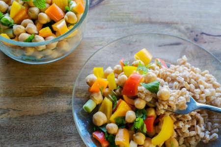Een vork die een gedeelte van farro, en garbanzo boonsalade, met een kom kikkererwtenensalade op de achtergrond, op houten lijst oproept - gezond veganist het eten concept