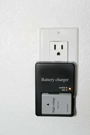 Grey, used, rechargeable lithium battery charging in a black rectangular battery charger plugged to an outlet on a white wall