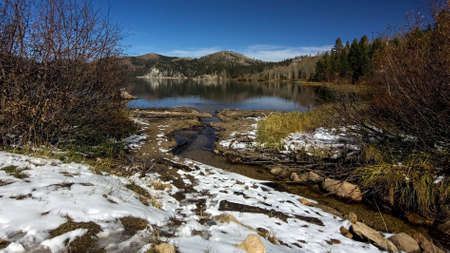 Overview of Marlette Lake in the fall, highlighting yellow vegetation and a thin layer of snow on the ground, against blue sky Stock Photo
