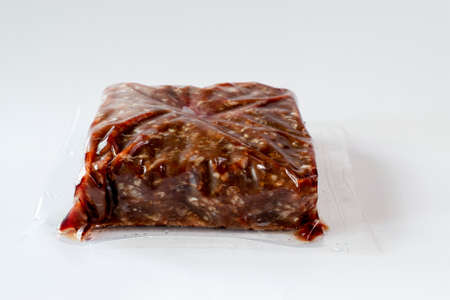 Ground frozen venison meat wrapped in plastic against white background