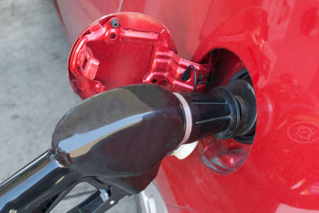 Closeup on a black nozzle filling the tank of a red car with gasoline at a gas station Stock Photo