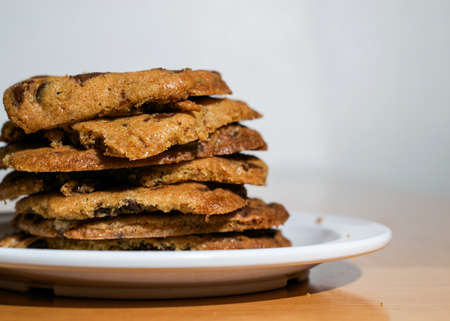 Closeup on stack of chocolate Chip Cookies in white plate on wooden table
