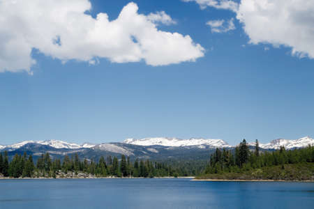 Sierra Nevada Ice House Reservoir in the spring of 2017, featuring snow in the mountain peaks and clouds in the sky Stock Photo