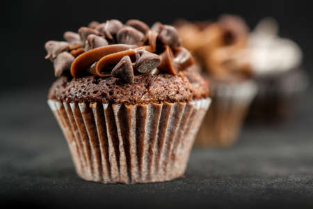 Three chocolate cupcakes garnished with chocolate chips and frosting on lined up across the frame, on black background Stock Photo