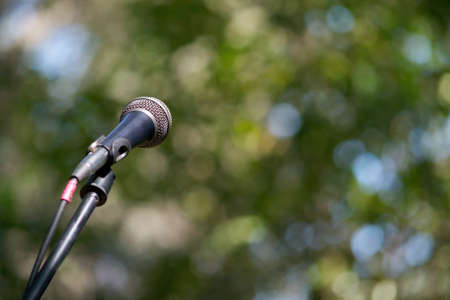 Selective focus on a microphone outdoors and lots of copyspace