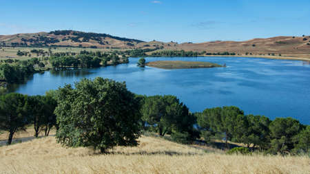 Panoramic view of the Lagoon Valley Park in Vacaville, California, USA, featuring the chaparral in the spring, with golden grass, and the lake Stock Photo