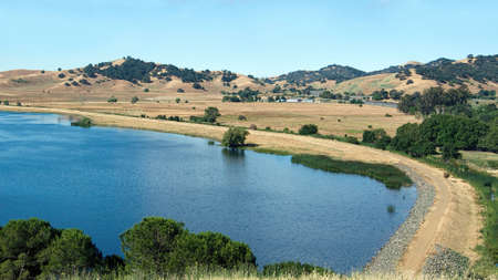 Panoramic view of the North side of the Lagoon Valley Park lake in Vacaville, California, USA, featuring the chaparral in the summer with golden grass and interstate-80 in the distance Stock Photo